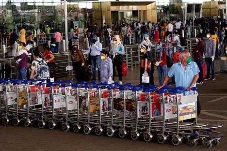 Kenttähenkilökunnan jäsen siirteli kärryjä Chhatrapati Shivajin lentokentällä Mumbaissa maanantaina.