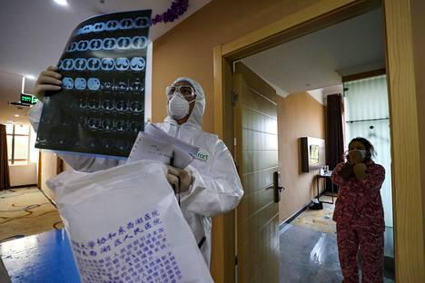 Lääkäri tarkasti potilaiden TT-kuvia wuhanilaisessa hotellissa, jonne oli eristetty epäiltyjä koronapotilaita.