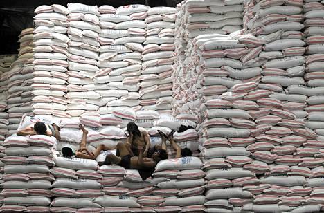 Työntekijät pitivät tauon riisisäkkien päällä Filippiinien elintarvikeviraston (National Food Authority) varastossa Taguigin kaupungissa tiistaina.