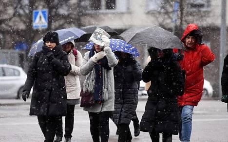 Jalankulkijoita lumisateessa Helsingissä maaliskuun lopussa.