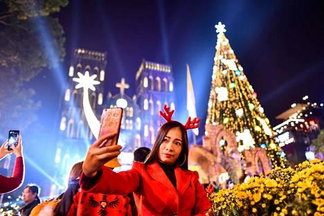 Sarvikoristeeseen sonnustautunut nainen kuvasi itseään joulukuusen ja juhlavalaistun katedraalin edustalla Vietnamin pääkaupungissa Hanoissa jouluaattona.