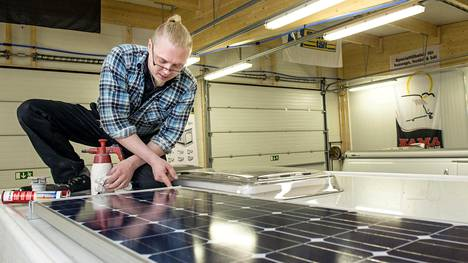 Tomi Annala asentaa asuntovaunun aurinkopaneelia paikalleen.