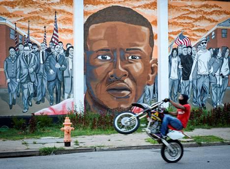 Moottoripyöräilijä ohitti poliisin käsissä kuollutta Freddie Grayta esittävän seinämaalauksen Yhdysvaltain Baltimoressa heinäkuussa 2016.