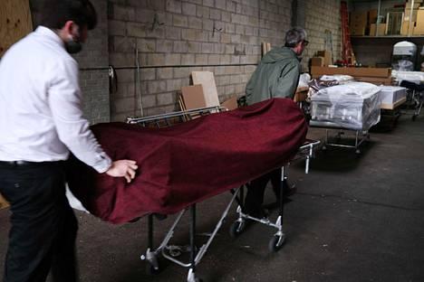 Covid-19-tautiin kuolleen ihmisen ruumista kuljetettiin kylmäsäilytykseen New Yorkin kaupungin Queensissa keskiviikkona.