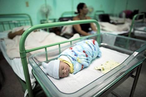 Vastasyntynyt vauva lepää äitinsä vieressä kuubalaisessa sairaalassa kesäkuussa. WHO julisti tiistaina Kuuban maailman ensimmäiseksi maaksi, joka on onnistunut lopettamaan hi-viruksen tarttumisen äideiltä lapsille.