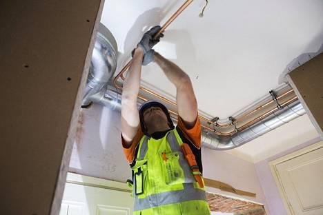Maxim Antonov asentaa kupariputkia kattoon putkiremontoitavassa talossa Helsingin Kalliossa.