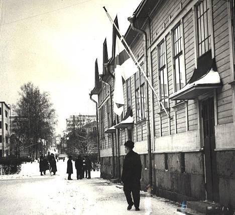 Hapelähteenkadun edusta oli koko eilisen päivän ajan satojen uteliaiden kuopiolaisten vierailujen kohteena, ja poliisiviranomaiset joutuivatkin alinomaa häätämään asiaankuulumattomia sivummalle. Apeaa tunnelmaa korosti puolitangossa oleva Suomen lippu.