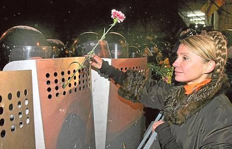 Julija Tymošenko ojensi kukan poliisille vuoden 2004 mielenosoituksissa.