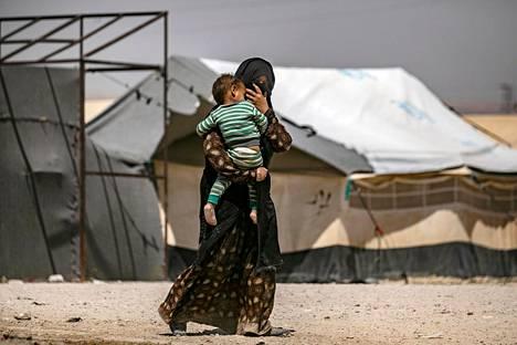 Nainen kantoi lasta al-Holin leirillä Syyriassa kesäkuun alussa.