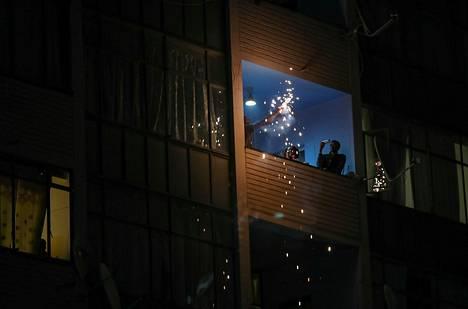 Ihmisiä parvekkeella juhlimassa uutta vuotta Johannesburgissa, Etelä-Afrikassa.