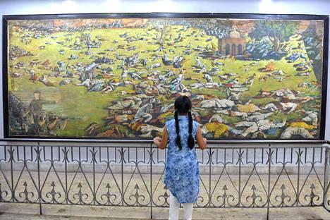 Intialaistyttö katseli Amritsarin verilöylyä esittävää maalausta Amritsarissa 7. huhtikuuta 2019.
