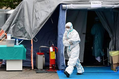 Brescian sairaalan työntekijä käveli ulos koronaviruspotilaita varten pystytetystä teltasta.