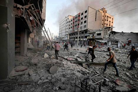 Ihmiset kerääntyivät Al-Shuruk-tornitalon romahtamisen jälkeen kaduille Gazassa.