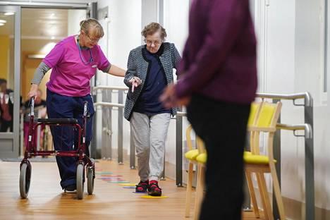 Fysioterapeutti Katja Räsänen auttaa Helvi Kuittista kulkemaan tasapainorataa pitkin. Käytävä kuntosalilta muihin yhteisiin tiloihin on tarkoituksella kalteva.