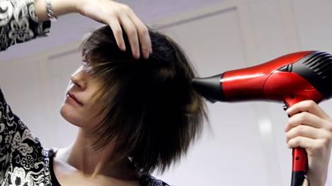 Moni suihkii hiuksiin lämpösuojaa ennen föönaamista.