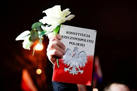 Mielenosoittaja piteli kädessään kukkaa ja Puolan perustuslakia Krakovassa perjantaina.
