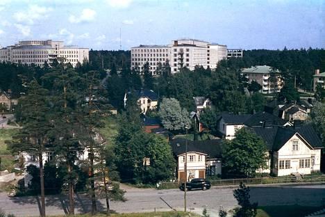 Puutalojen Ruskeasuo kuvattuna Koroistentien suunnasta. Kuvauspaikka sijaitsee nykyisen Koroistentie 8:n päädyssä. Taustalla erottuu Invalidisääätiö ja Ruskeasuon koulu.