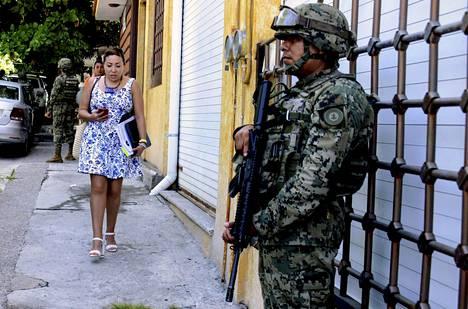 Jalankulkija ohittaa jalkakäytävällä Meksikon laivaston sotilaan syyskuun lopussa Acapulcossa. Sotilaat vastasivat kaupungin valvonnasta, kun paikallispoliisia epäiltiin kytköksistä huumekauppaan.