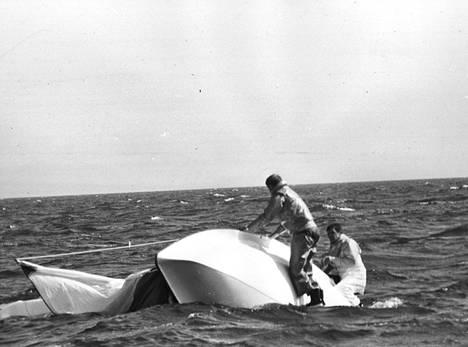 """Toisen lähdön puuskaisissa 5 boforin sivutuulissa lähtivät Turun ASS:ia edustavat Henrik von Knorring ja C. C. """"Burre"""" Trapp rajuun spinaakkerileikkiin, josta oli seurauksena veneen kaatuminen. Pahin on jo ohi. Miehet kiipeävät parhaillaan rungolle ja hetken kuluttua on vene jälleen pystyssä, vaikka tuuli ja aallokko ovat voimakkaita. Juttuun tärväytyi monta hyvää sijaa - ja pahimmassa tapauksessa jopa Suomen mestaruus."""