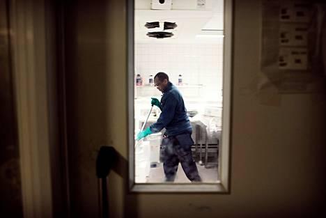 Keniasta lähtöisin oleva Michael Kiriama muutti Suomeen opiskelemaan vuonna 2005. Hienopuusepäksi valmistunut Kiriama ei ole löytänyt koulutusta vastaavaa työtä, vaan on työskennellyt siivoojana neljä vuotta. Kuvassa hän puhdistaa Stockmannin tavaratalon kylmiötä Helsingissä.