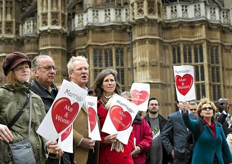 Homoliittojen vastustajat osoittivat mieltään parlamenttitalon edessä Lontoossa tiistaina.