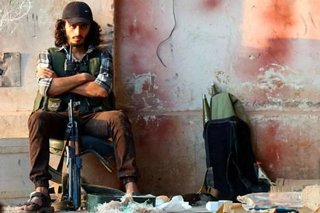 Kapinallistaistelija istui tykistökoulun edustalla Syyrian Aleppossa lauantaina.
