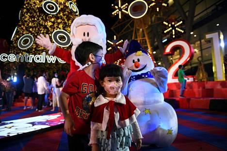 Maskeja käyttävät lapset kokoontuivat ostoskeskukseen, kun uudenvuoden lähtölaskennan juhlat ja ruuhkaiset tapahtumat kiellettiin koronavirustaudin takia Bangkokissa Thaimaassa.