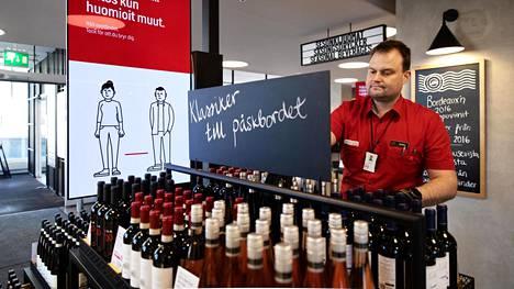 Myyjä Jouko Nieminen järjesti pulloja Arkadian Alkossa torstaina.