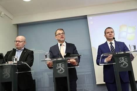 Työministeri Jari Lindström (sin), pääministeri Juha Sipilä (kesk) ja valtiovarainministeri Petteri Orpo (kok) torstain tiedotustilaisuudessa Kesärannassa.