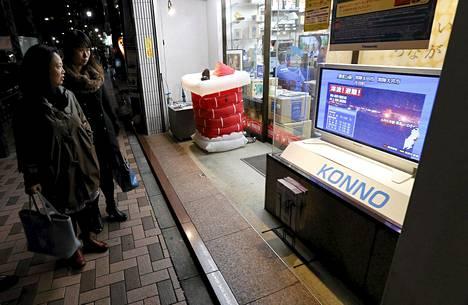 Ohikulkijat pysähtyivät perjantaina Tokiossa katsomaan suoraa lähetystä Iwakista, Fukushiman alueelta, jossa annettiin myös tsunamivaroitus.