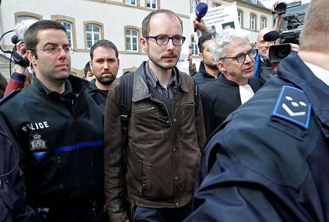 Poliisi saattoi Antoine Deltouria (kesk.) ja asianajaja William Bourdonia (oik.) oikeudenkäynnin jälkeen Luxemburgissa tiistaina.
