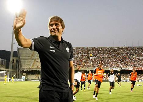 Juventuksen päävalmentaja Antonio Conte vilkuttaa faneilleen Juventuksen ystävyysottelussa Malaga CF:ää vastaan 4. elokuuta 2012.