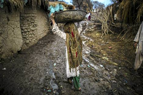 Afgaanityttö kantoi astiaa slummissa Islamabadin ulkopuolella.
