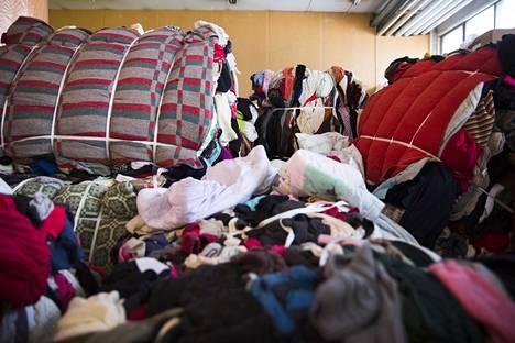 Kuluttajilta kerätyt tekstiilit kurottavat kohti kattoa Dafecorin varastossa.