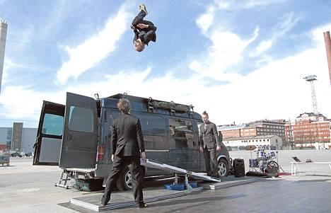 Esityksessä miehet hyppivät pakettiauton päälle vipulaudalta.