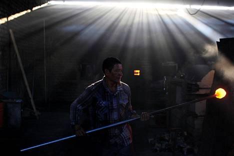 Lasinpuhaltaja pyörittää lasimassaa Cespedes-lasitehtaalla Olocuiltassa El Salvadorissa keskiviikkona.