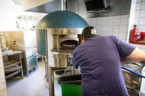 Daddy Greensin toinen omistaja Eero Kokkonen laittaa pitsan paistumaan Napolista hankittuun uuniin.