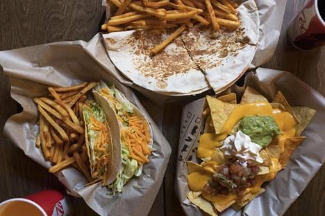 Taco Bellin antia: vasemmalla tacoja ja ranskalaisia perunoita, ylhäällä quesadilla ja oikealla nacholautanen juustokastikkeen ja dippien kanssa.