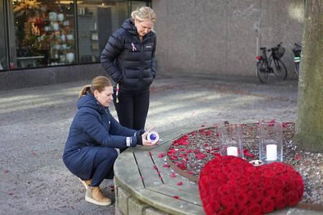 """Ulrika Lövfors ja Maria Jensmark sytyttivät kynttilän Vetlandan keskustan muistopaikalle torstaina. """"Väkivaltaa vastaan"""", Lövfors sanoi."""