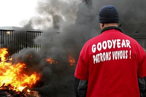 Goodyearin Amiensin-tehtaan työntekijät polttivat autonrenkaita protestiksi tehtaan portin edessä 18. marraskuuta viime vuonna. Paidan selässä nimitetään Goodyearin johtajia gangstereiksi.