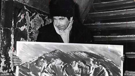 """Taiteilija maaliskuussa 1970. Alkuperäinen kuvateksti kertoo: """"Suomen viimeisen boheemin töitä on näytteillä tästä päivästä lähtien Tallin vintillä""""."""