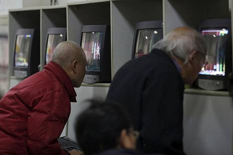 Sijoittajat seurasivat kurssikehitystä tietokoneruuduilta Shanghaissa perjantaina. Kurssikäyrät osoittivat aamupäivällä paikallista aikaa vaihteeksi ylöspäin.