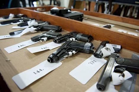 Poliisi huutokauppaa aseita Riihimäellä. Myytävien aseiden joukossa on myös aselupansa menettäneiden henkilöiden entisiä aseita. Kuva huutokaupasta vuodelta 2013.