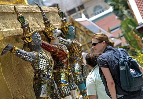 Turistit tutustuivat patsaisiin Bangkokissa tiistaina. Hätätilan poistamisen toivotaan houkutteleja turisteja takaisin maahan.
