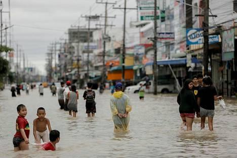 Ihmiset kahlasivat perjantaina veden peittämällä kadulla Nakhon Si Thammaratin alueella Etelä-Thaimaassa.