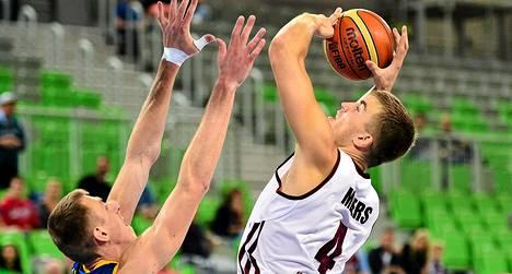 Latvian Martins Meiers (oik.) heittää ja Ukrainan Maxim Kornijenko puolustaa maiden välisessä EM-koripallon jatkosarjan ottelussa.