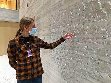 Viestintäasiantuntija Juha-Pekka Vanhatalo betoniin veistetyn kastepuun edessä. Rakkaus-teoksen lasihedelmiin kiinnitetään kastettujen lasten nimiä silkkinauhalla.