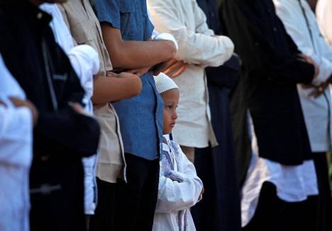 Poika kurkistaa aikuisten välistä Eid al-Fitr -juhlan rukoustilaisuudessa Sunda Kelapan satamakaupungissa Indonesiassa sunnuntaina.