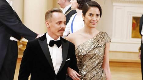 """Näyttelijä Jasper Pääkkönen saapui Linnan juhliin Alexandra Escatin kanssa, jonka paljettiasun on suunnitellut Mert Otsamo. Toispuoleiseen pukuun on kerrostettu  mustaa tylliä. Puvun teema käärme on Escatin mukaan """"hyvin symbolinen eläin""""."""