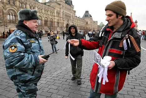 Opposition aktivisti tarjosi Venäjän omon-joukkojen miehelle valkoista nauhaa mielenosoituksessa sunnuntaina.